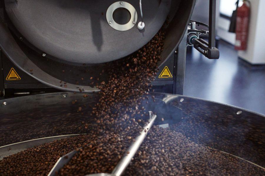 frisch gerösteter Kaffee kommt aus dem Trommelröster